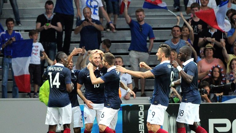France's forward Karim Benzema (C) is congratulated by teammates after scoring a goal during a friendly football match between France and Jamaica, on June