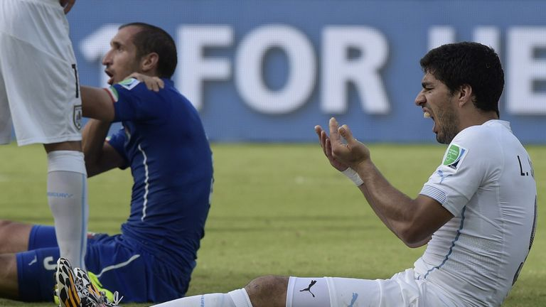 Uruguay's forward Luis Suarez (R) reacts past Italy's defender Giorgio Chiellini during a Group D football match