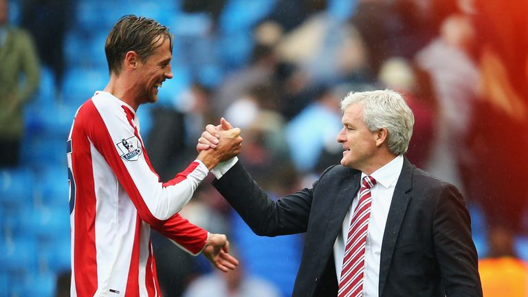 Peter Crouch of Stoke City celebrates victory with Mark Hughes