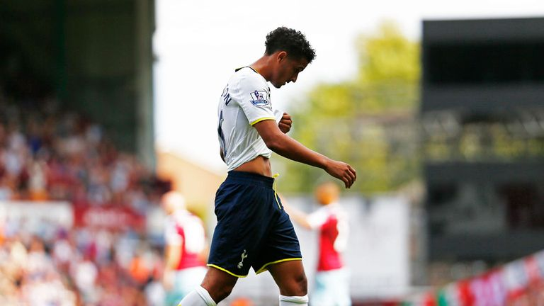 A dejected Kyle Naughton of Spurs walks off the pitch after receiving a red card for handball