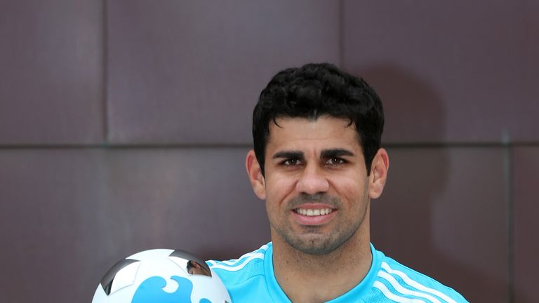 Chelsea striker Diego Costa celebrates with his Barclays Premier League Player of the Month award for August