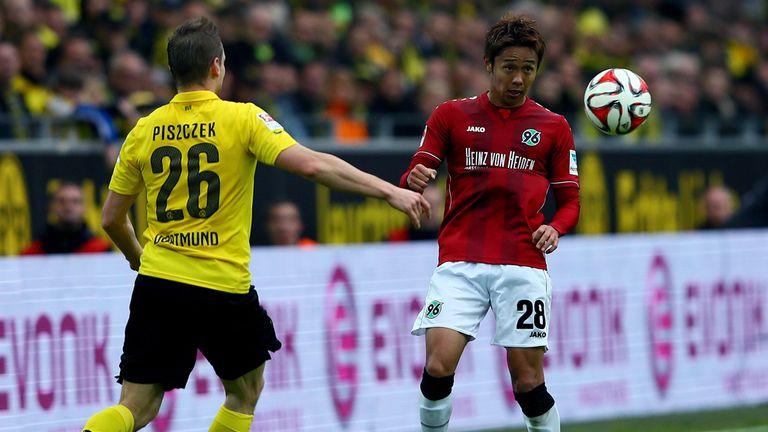 Lukasz Piszczek of Dortmund challenges Horoshi Kiyotake of Hannover