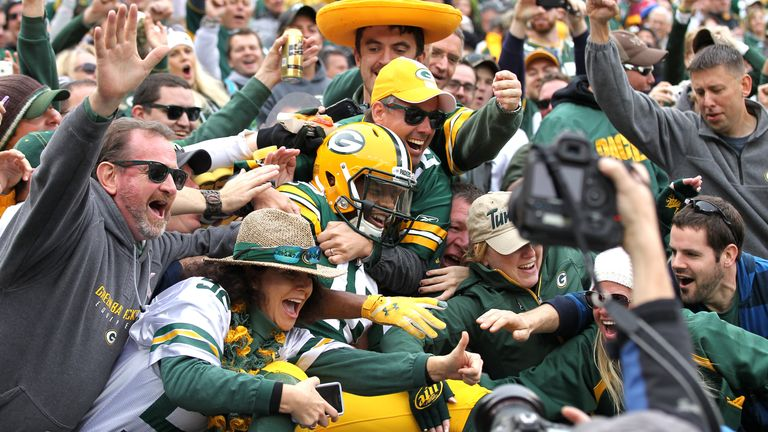 Randall Cobb does the famous 'Lambeau leap' with Packers fans