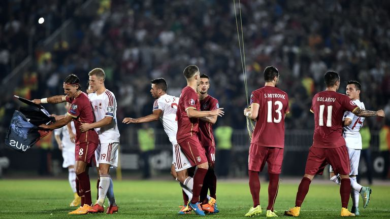 Serbia's and Albania players scuffle over a flag with Albanian national symbols pulled down by Serbia's defender Stefan Mitrovic (3rd R) from a drone