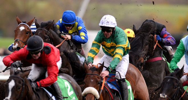 The runners jostle for position over the last with Johns Spirit in front and Caid Du Berlais (blue and yellow silks) in his slipstream.