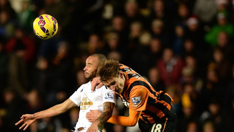 Ashley Richards of Swansea goes up for a header with Nikica Jelavic of Hull