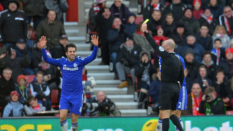 Chelsea midfielder Cesc Fabregas (L) reacts as referee Anthony Taylor (R) shows him a yellow card
