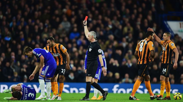 Referee Chris Foy shows a red card to Hull's Tom Huddlestone after a challenge on Filipe Luis