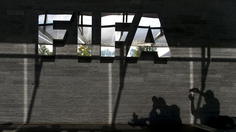 Shadows of journalists are seen next to a logo of the football's world governing body FIFA after a press conference on October 4, 2013 at ist headquarters