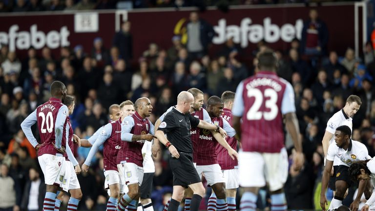 Aston Villa players surround the referee after he sent off Gabriel Agbonlahor
