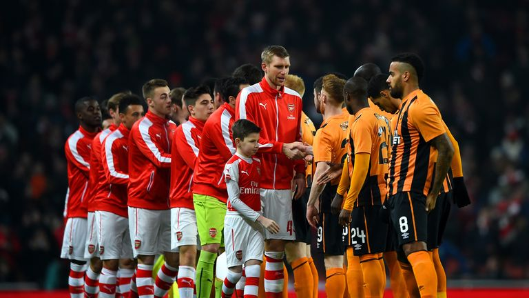 The Arsenal and Hull City players shake hands before the FA Cup Third Round match at the Emirates Stadium