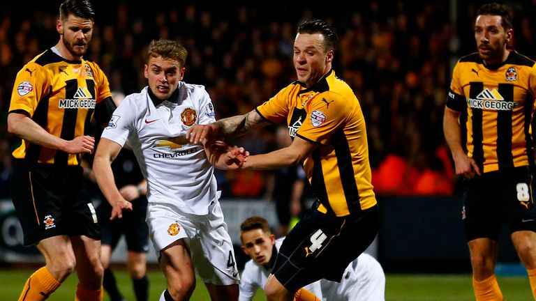 James Wilson of Manchester United battles for the ball with Josh Coulson of Cambridge United