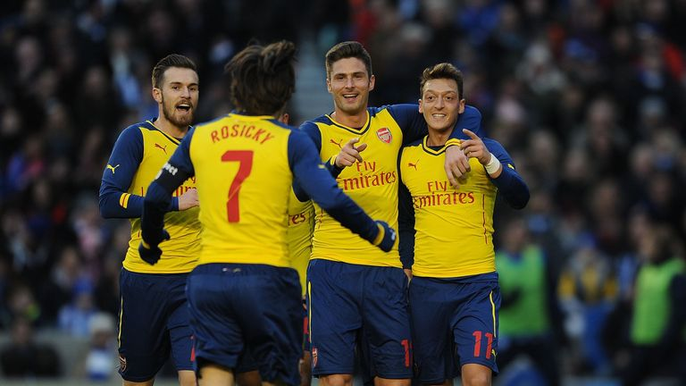 Mesut Ozil celebrates with his teammates after scoring Arsenal's second goal.