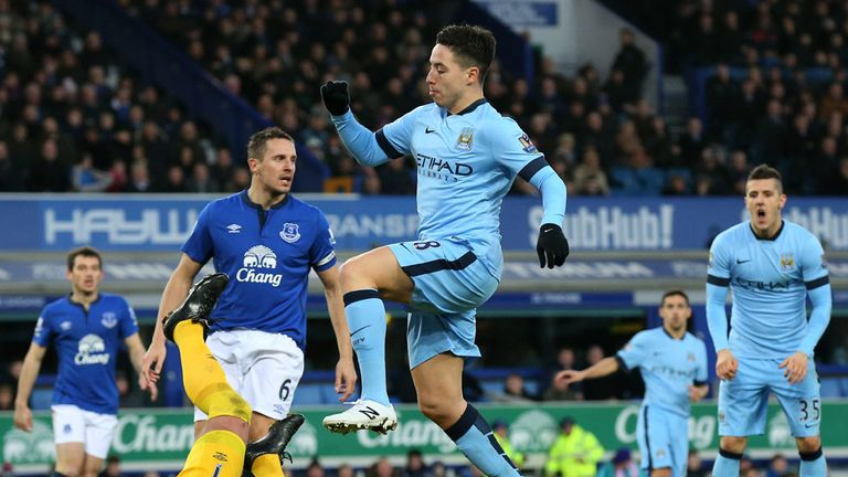 Goalkeeper Joel Robles of Everton pounces on the ball under pressure from Samir Nasri.