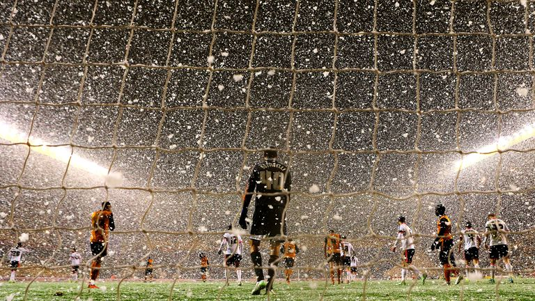 Snow falls during the FA Cup third round replay match.