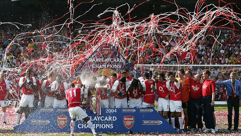 Sylvain Wiltord of Arsenal sprays his teammates with champagne as they celebrate winning the Premiership
