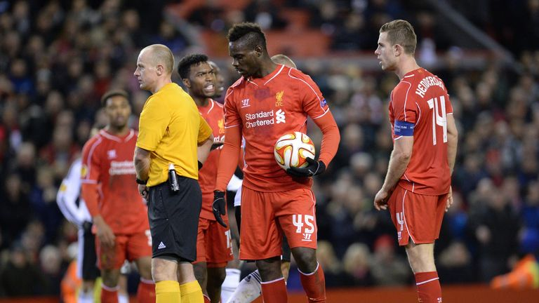 Liverpool's Mario Balotelli (C) holds the ball before placing it on the spot to take the kick and score after taking it from Jordan Henderson