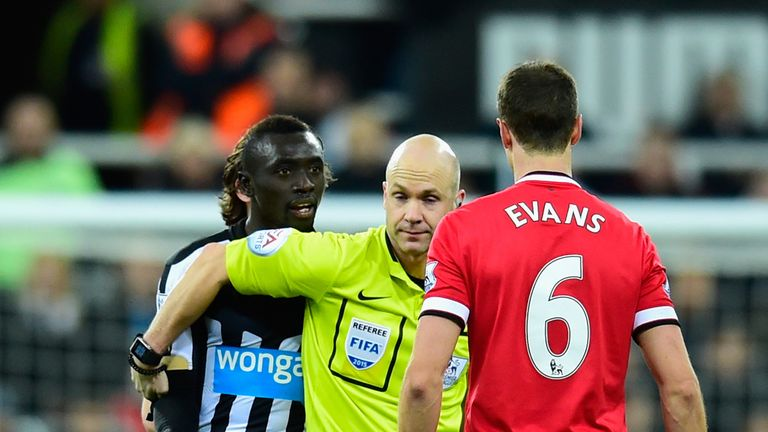 Referee Anthony Taylor steps in as Manchester United player Jonny Evans (c) and Papiss Cisse of Newcastle have words