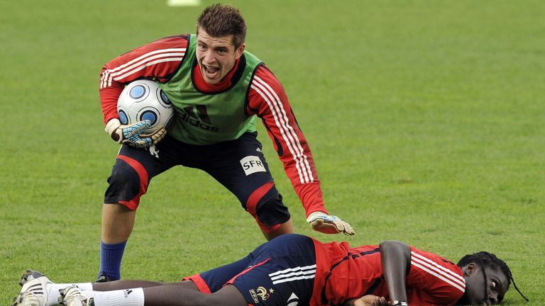 French national football team forward Bafetimbi Gomis (R) is helped by French Goalkeeper Cedric Carrasso after a vagal attack during a training session