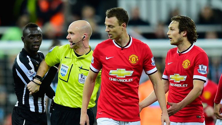 Referee Anthony Taylor steps in as Manchester United player Jonny Evans (c) and Papiss Cisse of Newcastle argue