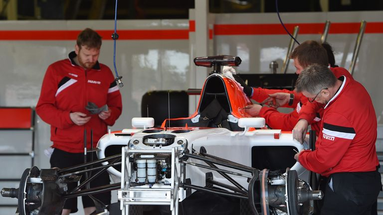 Manor work on their car in the garage in Australia