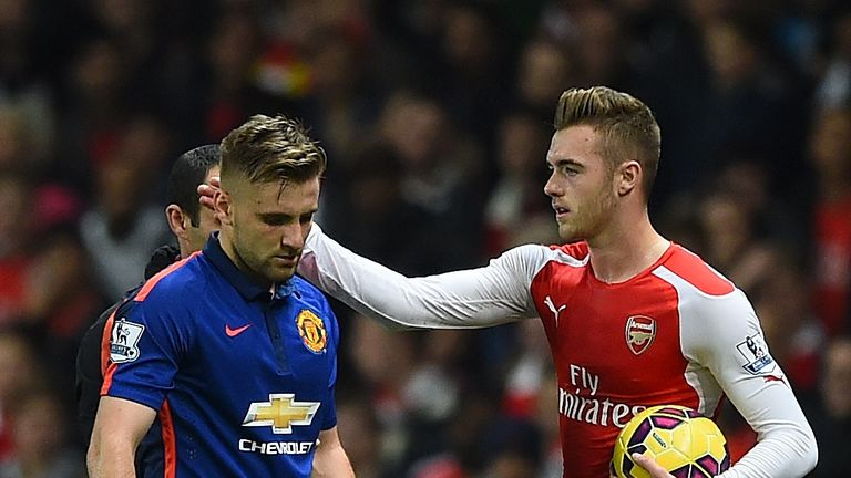 Calum Chambers of Arsenal gestures to Luke Shaw of Manchester United (L) as he walks off injured