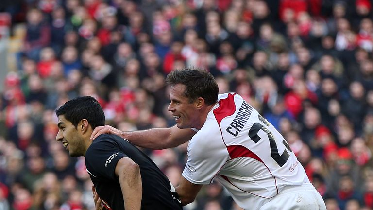Luis Suarez of the Gerrard XI tussles with Jamie Carragher of the Carragher XI during the Liverpool All-Star Charity match.