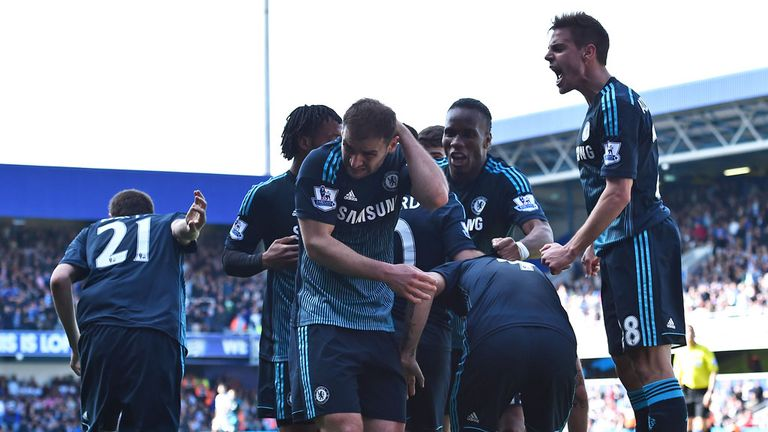 Branislav Ivanovic rubs his neck in pain as the rest of the Chelsea players celebrate a dramatic late winner at QPR