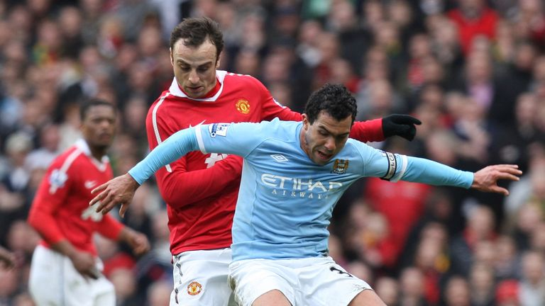 Dimitar Berbatov of Manchester United and Carlos Tevez of Manchester City compete for the ball at Old Trafford on February 12, 2011 in Manchester, England.