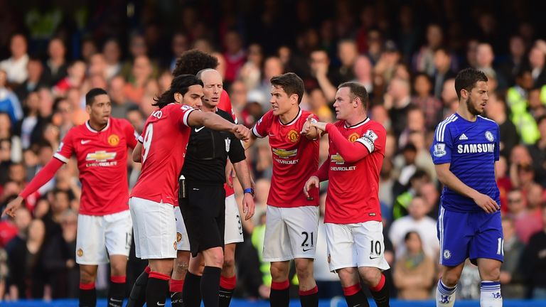 Referee Mike Dean is surrounded by Manchester United players last season