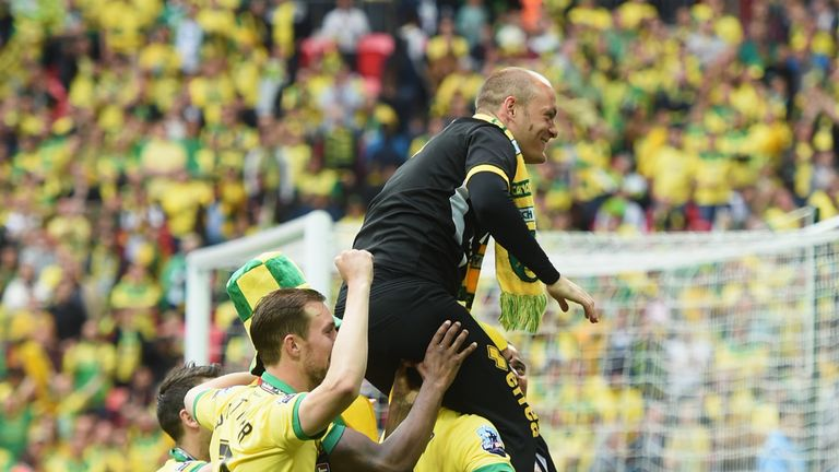 Alex Neil manager of Norwich City is carried by his players in celebration after the Sky Bet Championship Playoff Final between