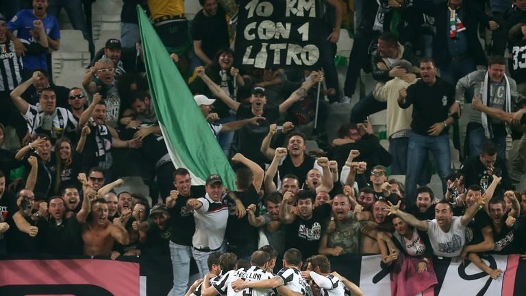 Juventus' forward from Spain Alvaro Morata (hidden) celebrates with teammates in front of fans after scoring
