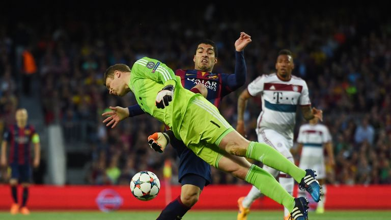 Luis Suarez of Barcelona and Manuel Neuer of Bayern Muenchen compete for the ball