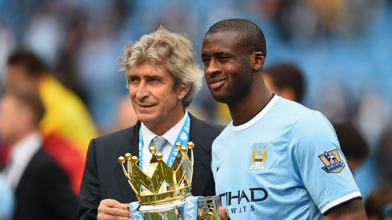 The Manchester City Manager Manuel Pellegrini and Yaya Toure pose with the trophy at the end of the Barclays Premier League