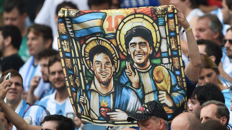 Argentina fan holds an image of Lionel Messi and Diego Maradona match against Nigeria at the Beira-Rio Stadium in Porto Alegre during the 2014 World Cup