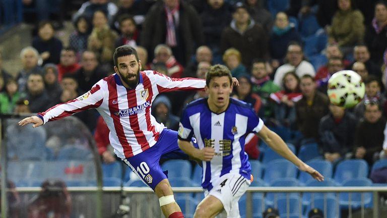 Atletico Madrid'smidfielder Arda Turan (L) kicks the ball