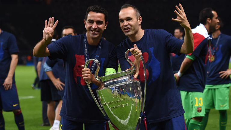 Barcelona's Xavi Hernandez and Andres Iniesta celebrate with the trophy after the UEFA Champions League Final football match against Juventus in June 2015