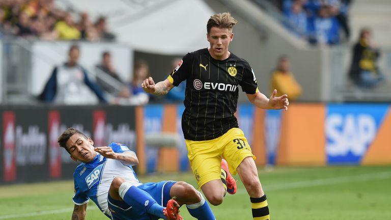 Erik Durm (R) of Dortmund is challenged by Roberto Firmino (L) of Hoffenheim