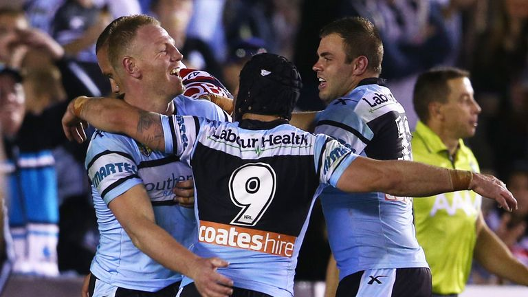 Luke Lewis, Michael Ennis and Wade Graham of Cronulla Sharks celebrate Lewis' try