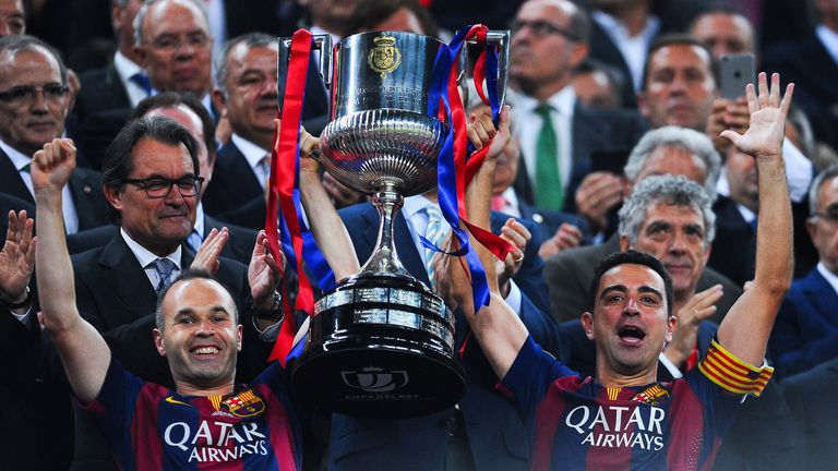 FC Barcelona players Andres Iniesta (L) and Xavi Hernandez of FC Barcelona celebrate with the trophy after winning the Copa del