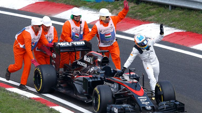 Fernando Alonso  pushes his McLaren car during qualifying for the Hungarian GP