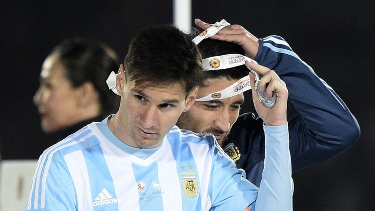 Argentina forward Lionel Messi (L) and defender Milton Casco take off second place medals of 2015 Copa America final in Santiago, Chile