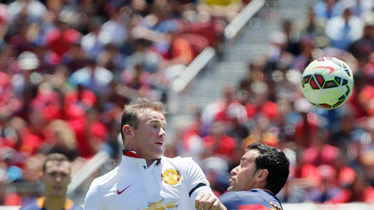 Wayne Rooney wins a header against Sergio Busquets