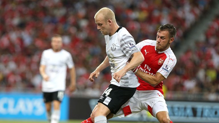 Steven Naismith is tackled by Aaron Ramsey as the players feel the heat in Singapore