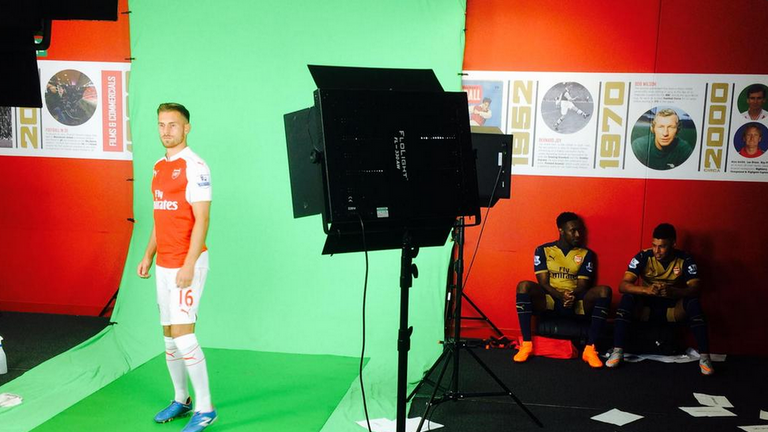 Arsenal's Aaron Ramsey filming pre-match graphics for Sky Sports. Danny Welbeck and Alex Oxlade-Chamberlain in background