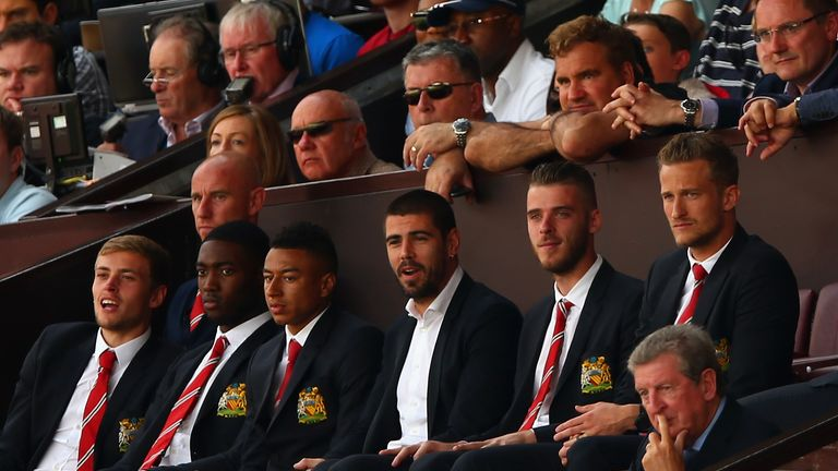 Manchester United players including goalkeepers David de Gea and Victor Valdes watch the game from the stands as Roy Hodgson watches from the row below