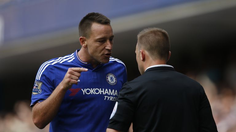 Chelsea's defender John Terry (left) talks with assistant referee Harry Lennard (right)