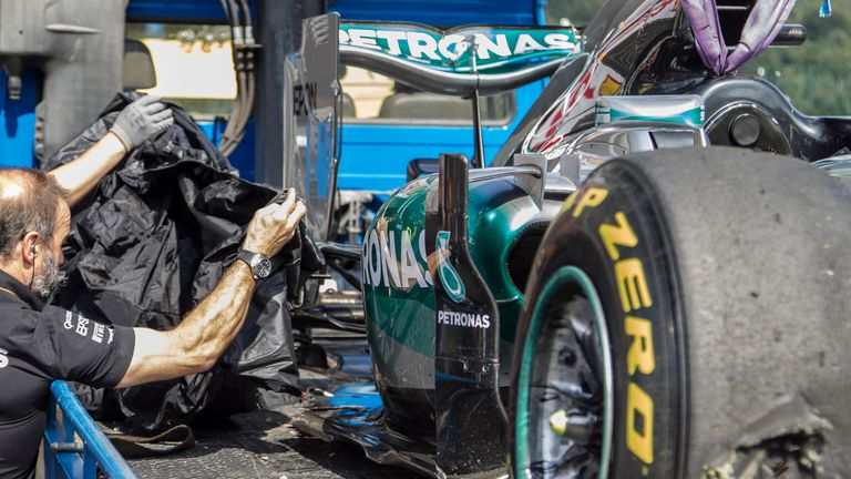 A Mercedes mechanic covers up the blown tyre on Nico Rosberg's W06