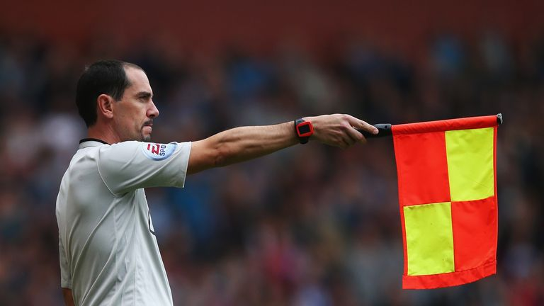 Assistant referee Stephen Child signals for offside