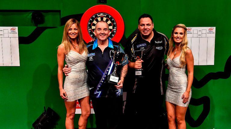 Phil Taylor (second left) celebrates his third successive Sydney Darts Masters title